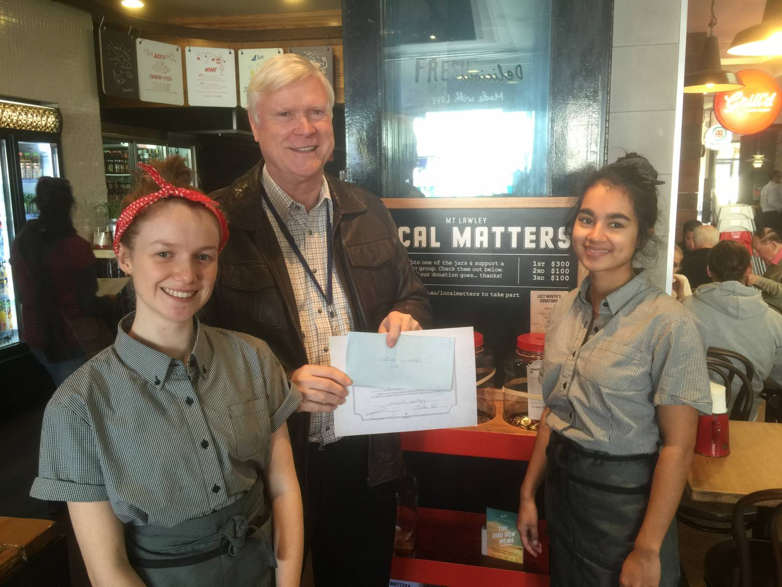 Kim Harrison, CEO, Crime Stoppers WA receiving the donation from staff at Grill'd, Mount Lawley